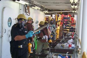 En 10 meter lang borekerne er netop hentet op fra dybhavsbunden i Stillehavet. Borekernen indeholder eksplosionsfarlig gas-is og giftig svovlbrinte, så forskerne bruger ansigtsværn og gasmasker. (Foto: 'IODP Expedition 201 Science Team')